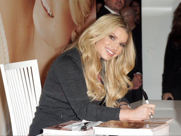 Jessica Simpson sitting at a table, signing autographs for her first memoir.