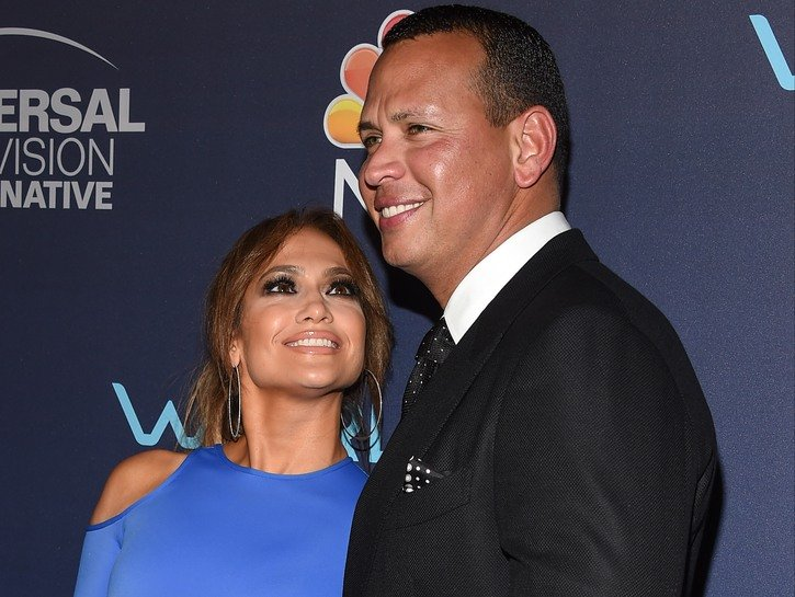 Jennifer Lopez in a blue dress looking up and smiling at Alex Rodriguez in a dark jacket.