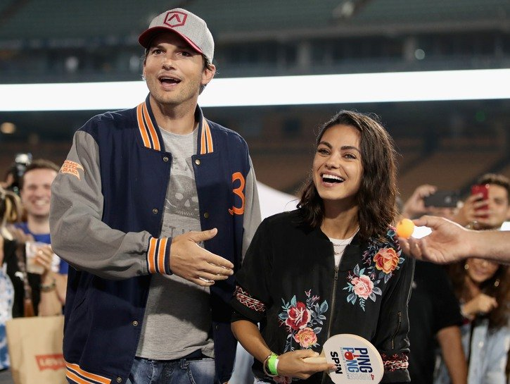 Ashton Kutcher on the left, smiling with Mila Kunis on the right holding a ping-pong paddle at a charity event.